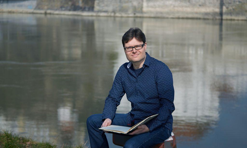 Philipp Ortmeier mit Notenheft an der Donau in Passau
